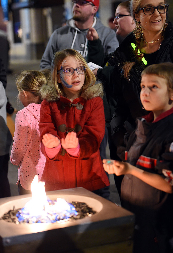 Audrey Nelson, 10, right, her mom Nicholette Everly, center, and Trystan Shunn, 8, right, warm up by the fire pit Wednesday, Nov. 29, 2017, during the Festival of Lights on Fourth Street in downtown Loveland.    (Photo by Jenny Sparks/Loveland Reporter-Herald)