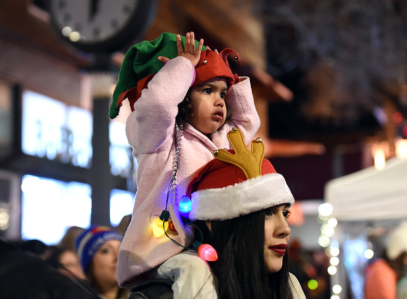 Mary Mcpheeters of Fort Collins, 2, sports an elf hat as she sits on her mother, Jessica Facio's shoulders Wednesday, Nov. 29, 2017, as the Chrtismas tree is lit during the Festival of Lights on Fourth Street in downtown Loveland.    (Photo by Jenny Sparks/Loveland Reporter-Herald)