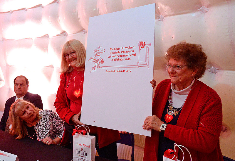 Corry McDowell, left, the 2019 Loveland valentine cache designer, left, and Marjean Carpenter, the 2019 cache verse author, unveil the 2019 cache and cache verse Thursday, Jan. 3, 2019, during the kick off to the Loveland Valentine Remailing Program at the Loveland Chamber of Commerce.  (Photo by Jenny Sparks/Loveland Reporter-Herald)