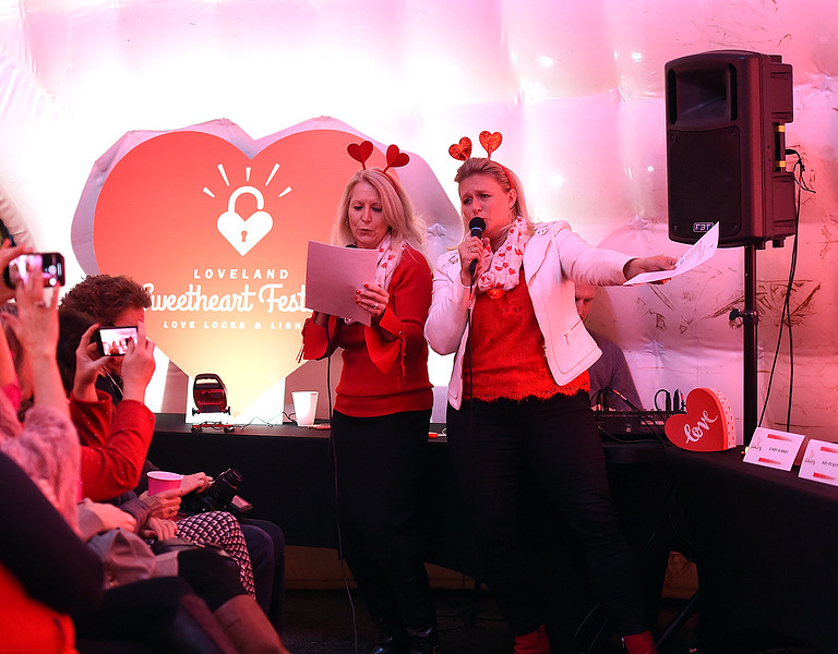 "Mindy McCloughan, President and CEO of the Loveland Chamber of Commerce, left, and Cindy Mackin, Loveland's Visitor Services Manager, right, sing their own version of ""The Love Boat"" song Thursday, Jan. 3, 2019, during the kick off to the Loveland Valentine Remailing Program at the Loveland Chamber of Commerce.  (Photo by Jenny Sparks/Loveland Reporter-Herald)"