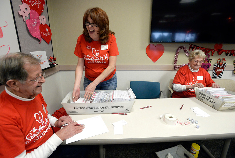 Chuck Crosby, left, Suzi Widick, center, and her mom, Carol Lemirande, share a laugh while working at the quality control table Wednesday, Feb. 1, 2017, during the kick off to the Loveland Valentine Re-Mailing Program at the Chamber of Commerce in east Loveland. (Photo by Jenny Sparks/Loveland Reporter-Herald)