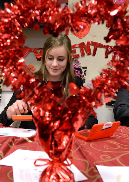Miss Loveland Valentine McKenna Dellinger is framed by a heart decoration as she stamps the first valentine Wednesday, Feb. 1, 2017, during the kick off to the Loveland Valentine Re-Mailing Program at the Chamber of Commerce in east Loveland. It is the 71st year of the re-mailing program where valentines from all over the world are sent to Loveland to be postmarked and stamped with a special cachet. (Photo by Jenny Sparks/Loveland Reporter-Herald)