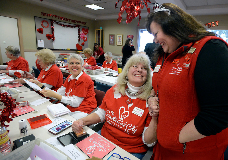 Jeanne Perrine, center right, and her daughter, Deanna Sloat, right, hold hands and chat Wednesday, Feb. 1, 2017, during the kick off to the Loveland Valentine Re-Mailing Program at the Chamber of Commerce in east Loveland. Sloat, a chamber ambassador and re-mailing program volunteer, has been helping stampers for six years and Perrine has been stamping for four years. (Photo by Jenny Sparks/Loveland Reporter-Herald)