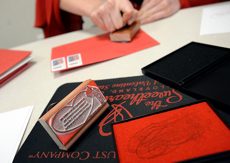 A stamp with the official 2018 Loveland Valentine cachet rests near an ink pad as Miss Loveland Valentine Ava McQuade stamps some of the first valentines Thursday, Feb. 1, 2018, during the kick-off to the valentine stamping  for the Loveland Valentine Re-mailing program at the Loveland Chamber of Commerce.    (Photo by Jenny Sparks/Loveland Reporter-Herald)