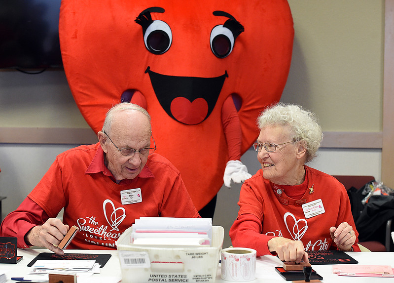Volunteers Ron Ford, left, and his wife, Mary Ellen Ford stamp Valentines Thursday, Feb. 1, 2018, during the kick-off to the valentine stamping  for the Loveland Valentine Re-mailing program at the Loveland Chamber of Commerce. The Fords have been stamping valentines off and on for 26 years.   (Photo by Jenny Sparks/Loveland Reporter-Herald)