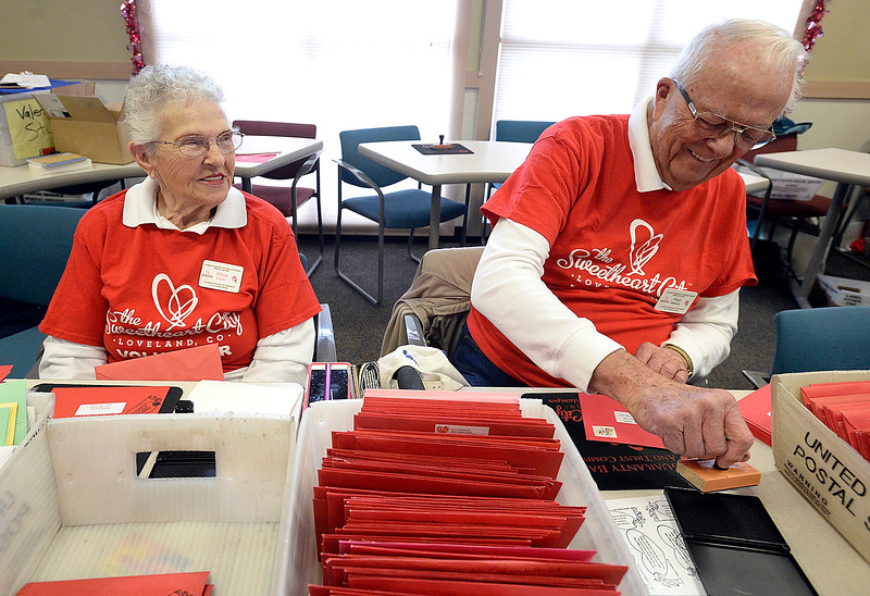 Wilma Davis, left, and Paul Wallace share a laugh as they stamp Valentines Thursday, Feb. 1, 2018, during the kick-off to the valentine stamping  for the Loveland Valentine Re-mailing program at the Loveland Chamber of Commerce. The two have been stamping valentines for three years.   (Photo by Jenny Sparks/Loveland Reporter-Herald)