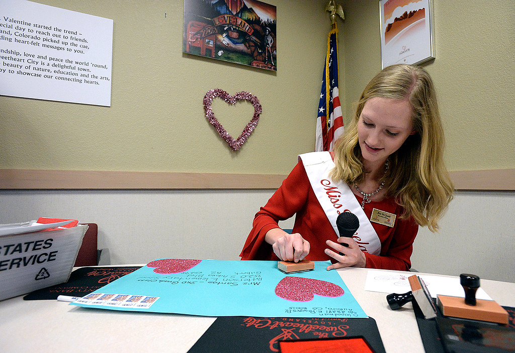. Miss Loveland Valentine Ava McQuade stamps some of the first valentines Thursday, Feb. 1, 2018, during the kick-off to the valentine stamping  for the Loveland Valentine Re-mailing program at the Loveland Chamber of Commerce.    (Photo by Jenny Sparks/Loveland Reporter-Herald)