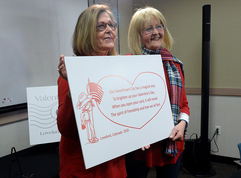 Judy Rethmeier, cachet verse author, left, and Cory McDowell, cachet designer, show off the Loveland 2018 Valentine cachet Tuesday, Jan. 2, 2018, during the unveiling of this year's card, cachet and verse for the Loveland Valentine Re-mailing program at the Loveland Chamber of Commerce in east Loveland. (Photo by Jenny Sparks/Loveland Reporter-Herald)