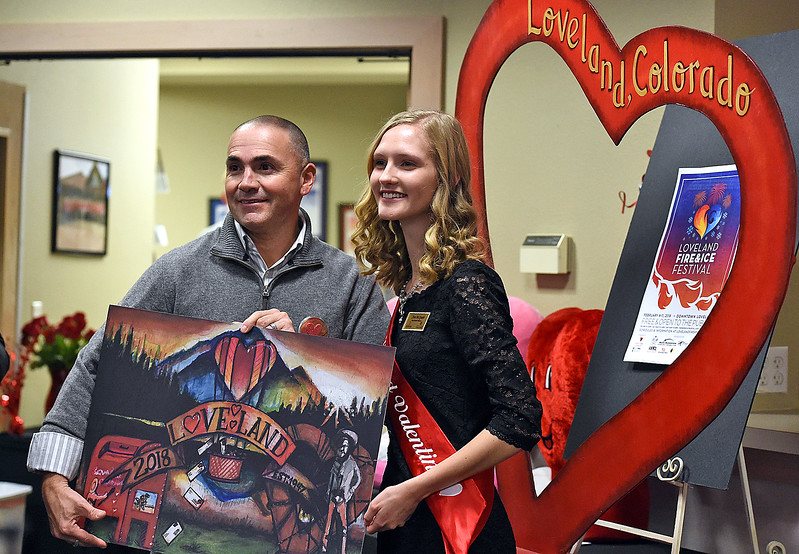 Chris Duran, the Loveland 2018 Valentine card designer, left, holds the card design as he and the 2018 Miss Loveland Valentine Ava McQuade speak to people Tuesday, Jan. 2, 2018, during the unveiling of this year's card, cachet and verse for the Loveland Valentine Re-mailing program at the Loveland Chamber of Commerce in east Loveland. (Photo by Jenny Sparks/Loveland Reporter-Herald)