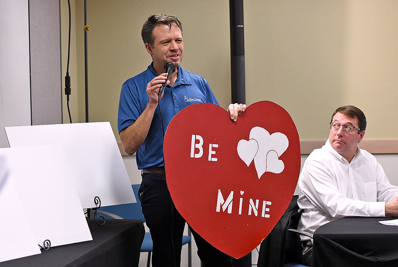Eric Weeding with Thompson Valley Rotary Club talks Tuesday, Jan. 2, 2018, about the hanging hearts for sale during the unveiling of this year's Valentine card, cachet and verse for the Loveland Valentine Re-mailing program at the Loveland Chamber of Commerce in east Loveland. (Photo by Jenny Sparks/Loveland Reporter-Herald)