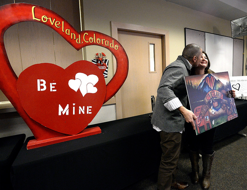 . Chris Duran, the Loveland 2018 Valentine card designer, left, holds the card design as he gives his wife, Valerie Duran, a smooch Tuesday, Jan. 2, 2018, during the unveiling of this year\'s card, cachet and verse for the Loveland Valentine Re-mailing program at the Loveland Chamber of Commerce in east Loveland. (Photo by Jenny Sparks/Loveland Reporter-Herald)