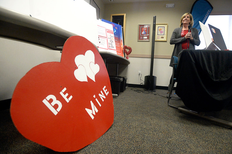 Lindsay Cantly witht the Thompson Valley Rotary Club talks about how people can buy wooden hearts during the official 2017 Loveland Valentine Remailing program's card, cachet and verse unveiling Tuesday, Jan 3, 2016, at the Loveland Chamber of Commerce. (Photo by Jenny Sparks/Loveland Reporter-Herald)