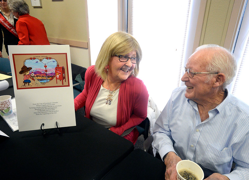 Corry McDowell, left, the Valentine card and card cachet designer, and James Duckworth, card cachet verse author, chat about the card and cachet during the official unveiling of the 2017 Valentine Remailing card, cachet, beer, coffee and more Tuesday, Jan 3, 2016, at the Loveland Chambr of Commerce. (Photo by Jenny Sparks/Loveland Reporter-Herald)