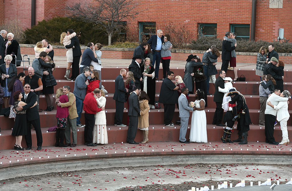. Couples smooch and make it official after being pronounced man and wife Tuesday, Feb. 14, 2017, during Loveland\'s first Valentine\'s Day group wedding at Foote Lagoon downtown.   (Photo by Jenny Sparks/Loveland Reporter-Herald)