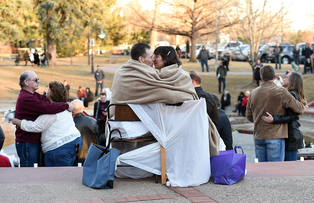. Sitting under a blanket in their wedding attire. Juan Basson, left, and Nina Rey snuggle and try to stay warm Tuesday, Feb. 14, 2017, before getting hitched at Loveland\'s first Valentine\'s Day group wedding at Foote Lagoon downtown.   (Photo by Jenny Sparks/Loveland Reporter-Herald)