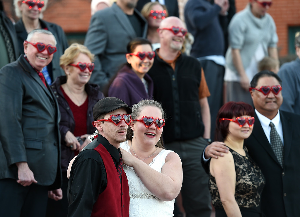 . Surrounded by other couples sporting heart sunglasses, Duane Kosobud, left, and his wife, Sonnie Jones, both of Loveland, smile after being pronounced man and wife Tuesday, Feb. 14, 2017, during Loveland\'s first Valentine\'s Day group wedding at Foote Lagoon downtown.   (Photo by Jenny Sparks/Loveland Reporter-Herald)