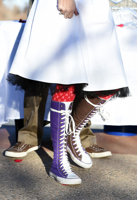 . Sporting the same Knee-high converse she got married in the first time, Jenn Headlee of Loveland and her groom, Adam Headlee, behind her, walk towards Foote Lagoon Tuesday, Feb. 14, 2017, during Loveland\'s first Valentine\'s Day group wedding. The two, who were first married in 2013, renew their vows every year.  (Photo by Jenny Sparks/Loveland Reporter-Herald)