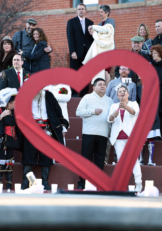 . Mystic Archambeau, right, is framed by a heart as she takes a selfie of herself and her groom Tuesday, Feb. 14, 2017, during Loveland\'s first Valentine\'s Day group wedding at Foote Lagoon downtown.   (Photo by Jenny Sparks/Loveland Reporter-Herald)