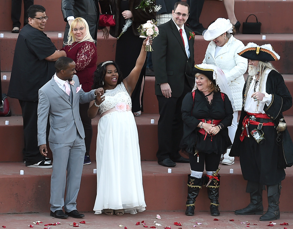 . New bride India Thomas. left, cheers after she and her husband, Mark Perkins, and numerous other couples tied the knot Tuesday, Feb. 14, 2017, during Loveland\'s first Valentine\'s Day group wedding at Foote Lagoon downtown. Bernie and Duane Littlefield of Loveland, right, dressed as pirates to renew their vows, and other couples smile at the cheer.  (Photo by Jenny Sparks/Loveland Reporter-Herald)