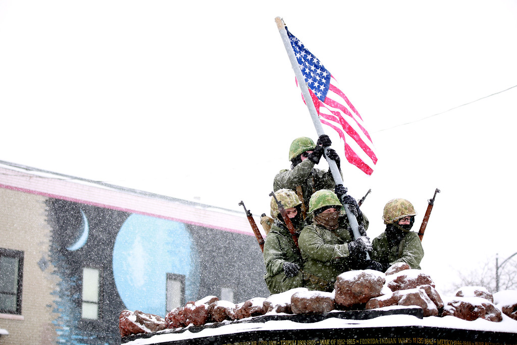 . Cade Colburn, Nate Godely, Josh Gischel and Seth Anderson reenact the famous photo of soldiers raising the flag in Iwo Jima during the annual Veterans Day Parade in Loveland, Colo. on Nov. 11, 2018. Photo by Taelyn Livingston/ Loveland Reporter-Herald