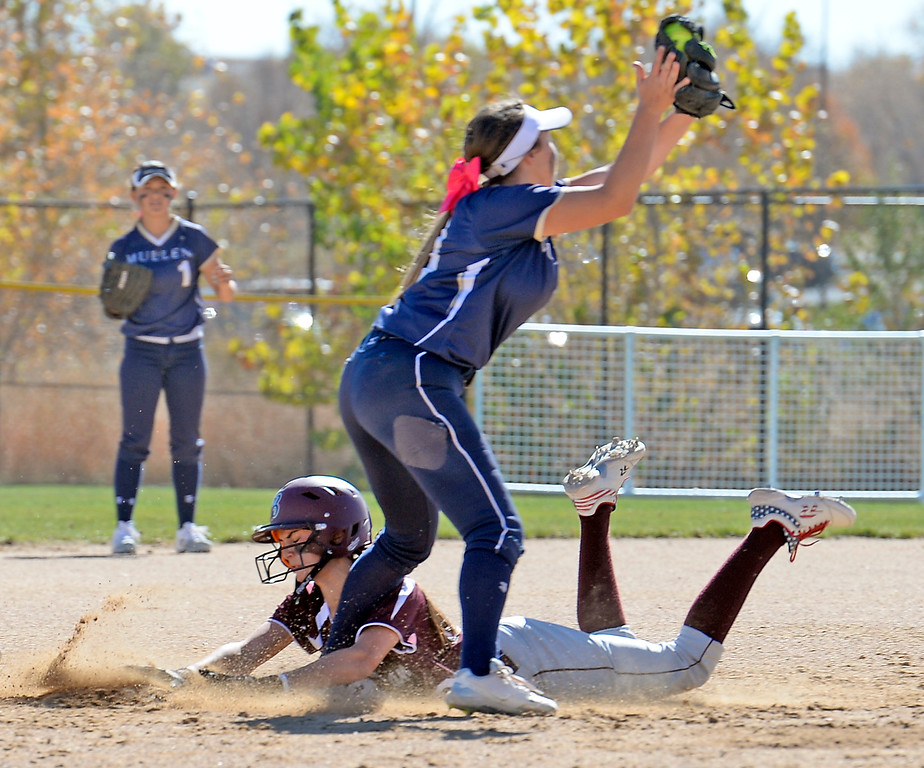 Berthoud's #00 Sotera Dageenakis slides into third base as Mullen's #13 CharliRose Davis catches the ball during their game at the 5A State Softball championships at the Aurora Sports Park on Friday, Oct. 21, 2016. (Photo by Jenny Sparks/Loveland Reporter-Herald)