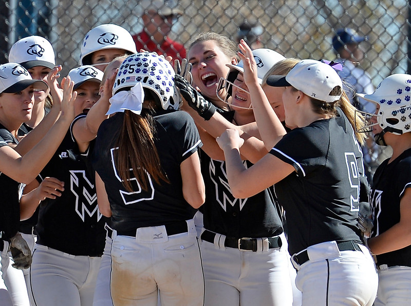 The Mountain View softball team mobs #5 Izzy Griego after a homerun during their game against Discovery Canyon at the 5A State Softball championships at the Aurora Sports Park on Friday, Oct. 21, 2016. (Photo by Jenny Sparks/Loveland Reporter-Herald)