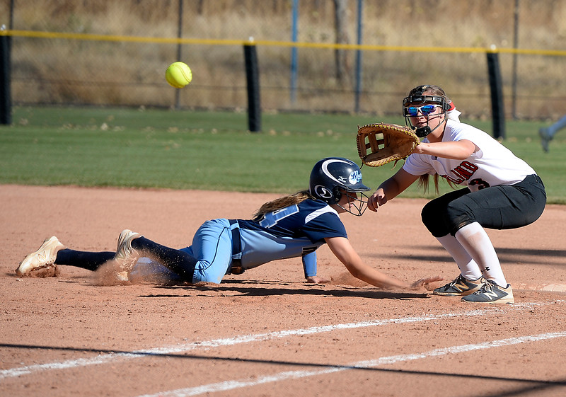 Loveland High School's #3 Addi Woodard keeps her eye on the ball as Ralston Valley's #24 Christaana Angelopulos slides into first base during their game at the 5A State Softball championships at the Aurora Sports Park on Friday, Oct. 21, 2016. (Photo by Jenny Sparks/Loveland Reporter-Herald)