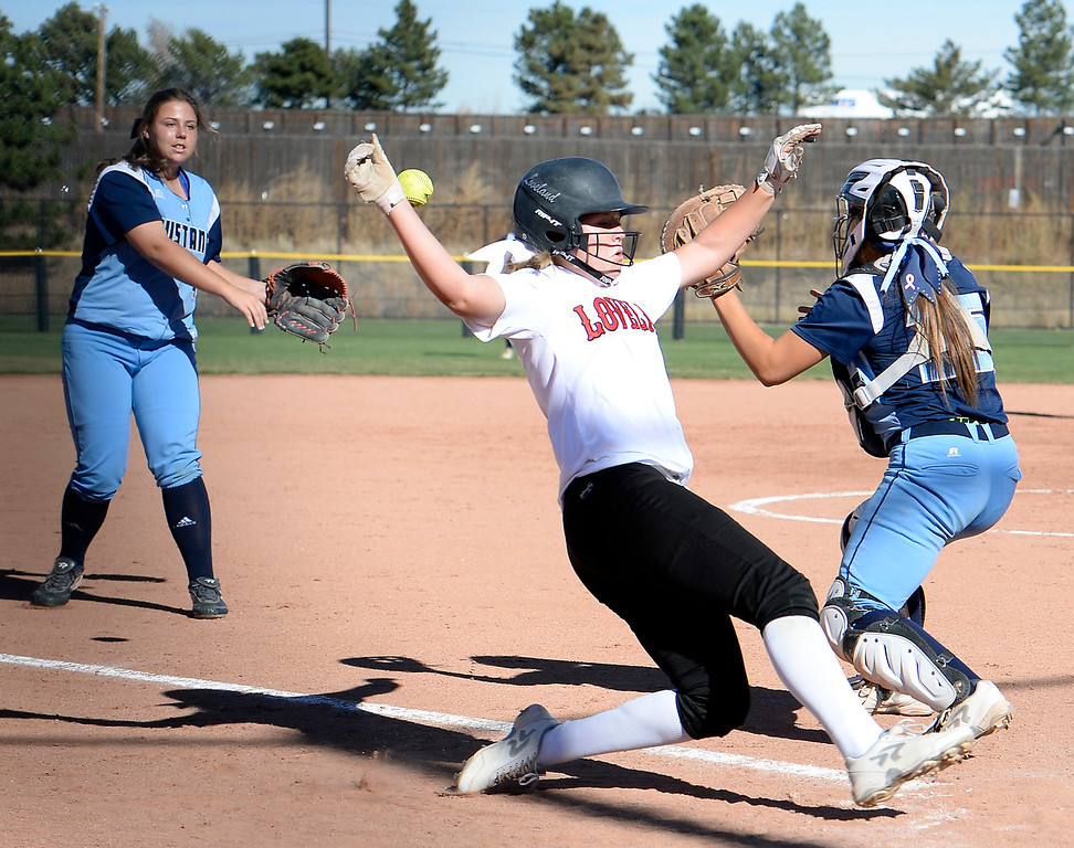 Loveland High School's #9 Abby Anderson slides into home past Ralston Valley's catcher Alexa Samuels during their game the 5A State Softball championships at the Aurora Sports Park on Friday, Oct. 21, 2016. (Photo by Jenny Sparks/Loveland Reporter-Herald)