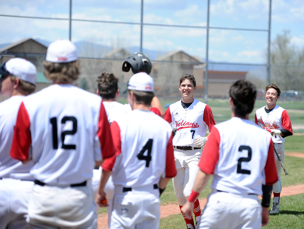 . Zach Harstad is greeted by his teammates after launching a two-run home run in the first inning against Greely West on Saturday, May 4. The Indians won 6-1 on senior day. (Colin Barnard/Loveland Reporter-Herald)