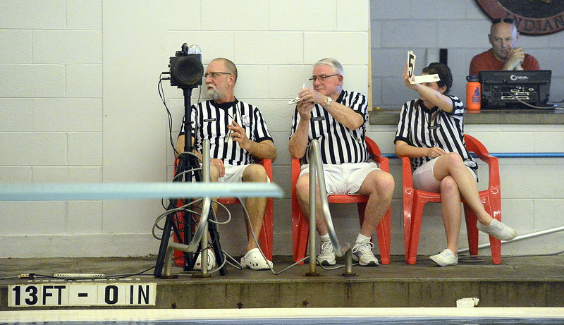 The meet officials flash their scores for the final attempt of Loveland diver James Greenup's six-dive set during Tuesday's meet with Fort Collins at the LHS pool. (Mike Brohard/Reporter-Herald).