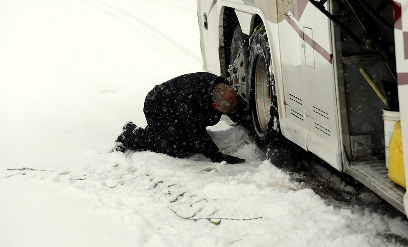 Getting mixed signals from road signs, bus driver Chris McCay decided it was better to be prepared, stopping at the mouth of the Eisenhower Tunnel to put on chains, with assistance from Loveland coach Wayne McGinn. McCay then stopped in Silverthorne to take them off when it was clear they were not needed. (Mike Brohard/Loveland Reporter-Herald)