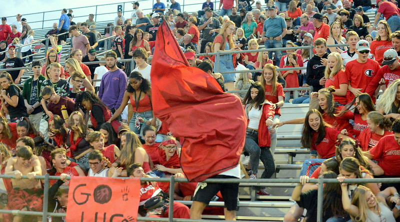 Loveland's Jack Peden slams the spirit flag into the stands, making the crowd part at halftime of Thursday's 4A football game between No. 2 Loveland and No. 3 Broomfield at Patterson Stadium. (Mike Brohard/Loveland Reporter-Herald)