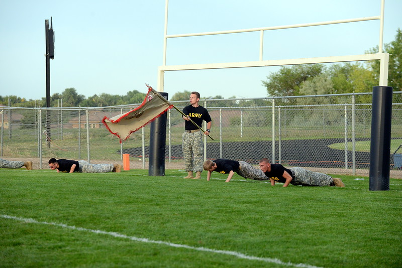 Members of the Loveland High School ROTC bang out pushups for each point the Indians's scored in a 47-0 romp of Broomfield on Thursday at Patterson Stadium. (Mike Brohard/Loveland Reporter-Herald)