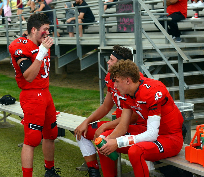 Loveland's Jordan Cardenas (50) talks with teammates Riley Kinney (2) and Brendan Bower on the sidelines of Thursday's game with Broomfield at Patterson Stadium. (Mike Brohard/Loveland Reporter-Herald)