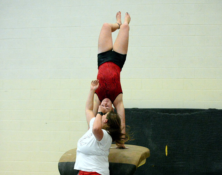 Loveland coach Jessica Toomey spots Jadyn Krier as she works on her vault in practice. (Mike Brohard/Loveland Reporter-Herald)