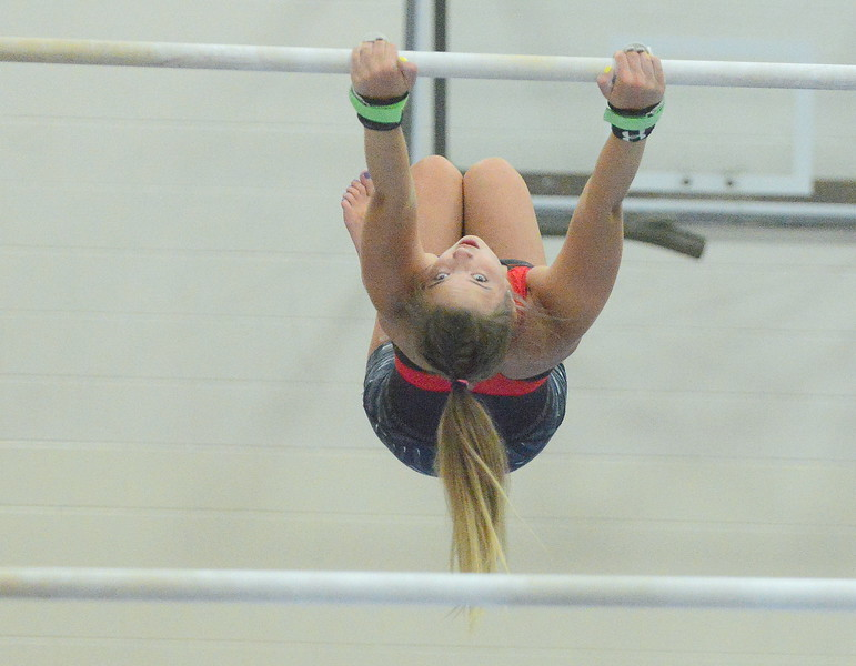 Katie Smith gets ready to release the top bar for her dismount at practice. (Mike Brohard/Loveland Reporter-Herald)