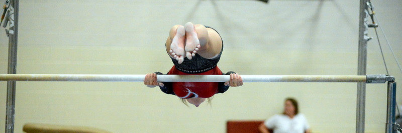 Halle White gets parallel as she works on her uneven bars routine in practice. (Mike Brohard/Loveland Reporter-Herald)