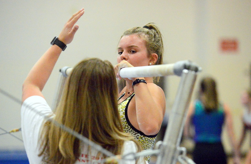 Maya McQuigg listens to Loveland gymnastics coach Jessica Toomey as she gives instruction on the uneven bars at a recent practice. The Indians placed sixth as a team in 4A in 2017, and the squad is looking for a return trip to the final event in 2018. (Mike Brohard/Loveland Reporter-Herald)