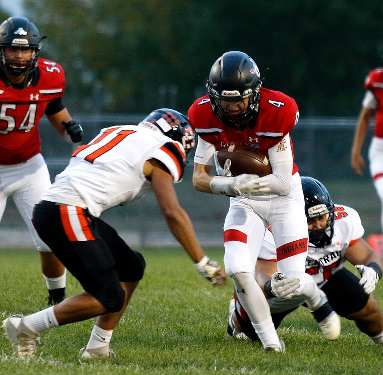 Loveland's Cody Rakowsky (4) pushed through Greeley Central's Xavier Bonham (11) as Ruben Castellanos (56) grabs his leg at Patterson Stadium in Loveland Friday, Sept. 15, 2017. (Photo by Lauren Cordova/Loveland Reporter-Herlad)
