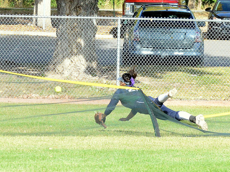 Pine Creek center fielder Gerilyn Martinez falls over the temporary fence in pursuit of a home run hit by Loveland's Allison Westbrook  during Saturday's game at the 5A Region 4 tournament at the Barnes Complex in Loveland. The Indians won 9-2. (Mike Brohard/Loveland Reporter-Herald)