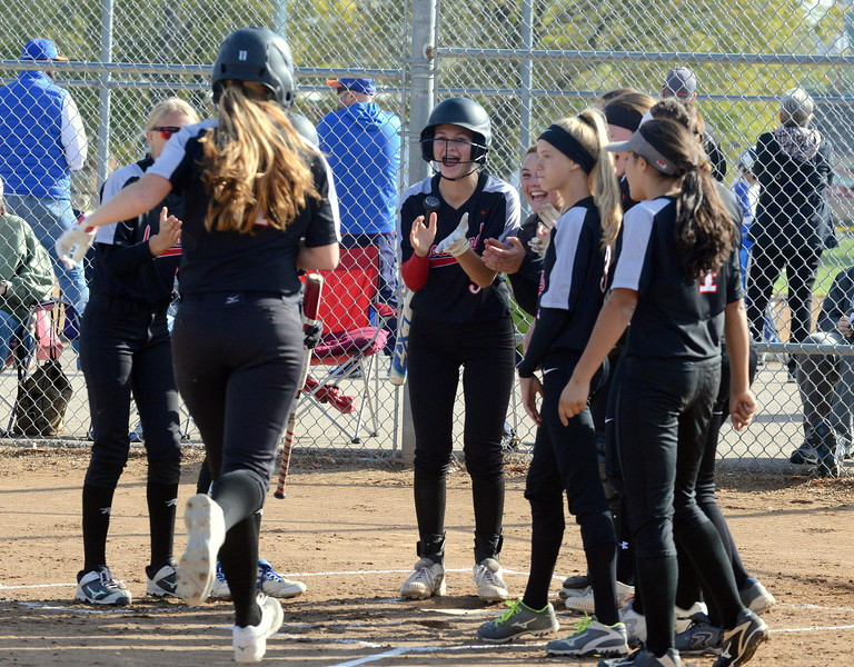 Loveland's bench empties to greet Allison Westbrook at home plate after her home run  during Saturday's game with Pine Creek at the 5A Region 4 tournament at the Barnes Complex in Loveland. The Indians won 9-2. (Mike Brohard/Loveland Reporter-Herald)