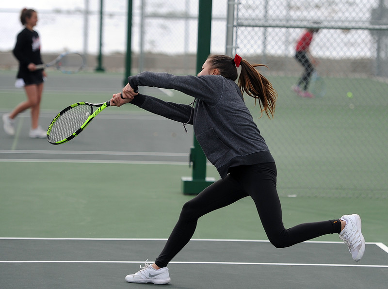 Tara Jeffries lunges for a backhand in the No. 3 doubles match at Loveland High School on Friday, April 12. Loveland lost to Fossil Ridge 5-2. (Colin Barnard/Loveland Reporter-Herald)