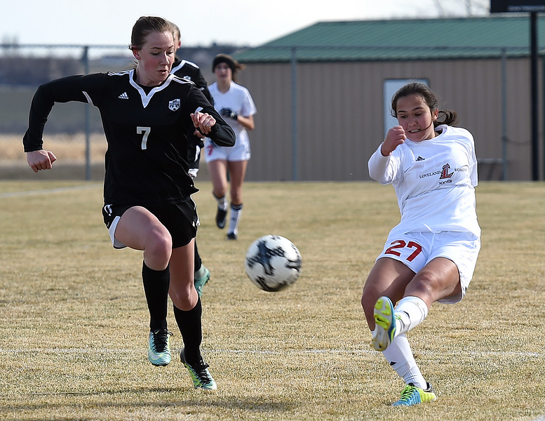 Loveland's (27) Megan Stackhouse kicks the ball past Berthoud's (7) Ashley Hiatt during their game Monday, March 19, 2018, at Mountain View High School in Loveland. (Photo by Jenny Sparks/Loveland Reporter-Herald)