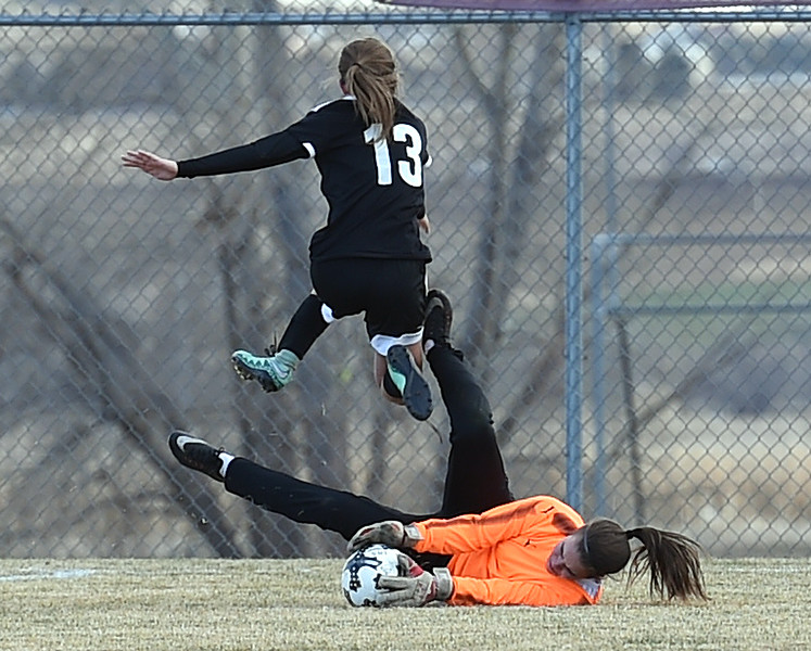 Loveland's goalie Jillian Cherry blocks as Berthoud's (13) Breanna Fowler jumps over her during their game Monday, March 19, 2018, at Mountain View High School in Loveland. (Photo by Jenny Sparks/Loveland Reporter-Herald)