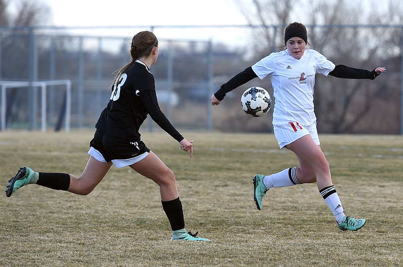 Berthoud's (13) Breanna Fowler and Loveland's (11) Mikayla Pennock battle for control of the ball during their game Monday, March 19, 2018, at Mountain View High School in Loveland. (Photo by Jenny Sparks/Loveland Reporter-Herald)