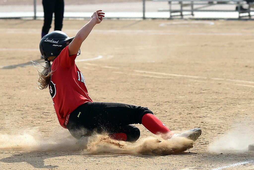 . Loveland High\'s (13) Kassi Reiger slides safely into third base Tuesday, Aug. 29, 2017, during their game against Boulder High at Centennial Park in Loveland. (Photo by Jenny Sparks/Loveland Reporter-Herald) l13