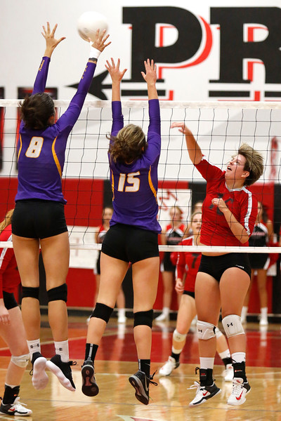 Loveland's Macie Losh (16) hits the ball as Boulder's Gabby Rucker (8) and Fiona Quinn (15) jump to block her hit at Loveland High School on Tuesday, Oct. 17, 2017. (Photo by Lauren Cordova/Loveland Reporter-Herald)
