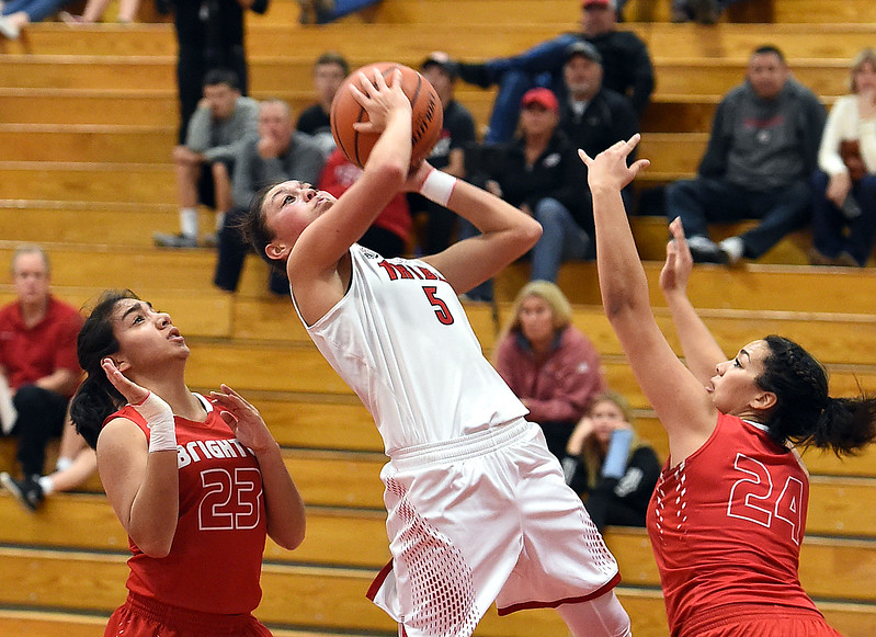 Loveland High's #5 Tatum Rembao goes up for a shot past Brighton's #23 Janae Reyes and #24 Kaylah Lewis during their game Tuesday, Feb. 21, 2017, at Loveland High School in Loveland. (Photo by Jenny Sparks/Loveland Reporter-Herald)
