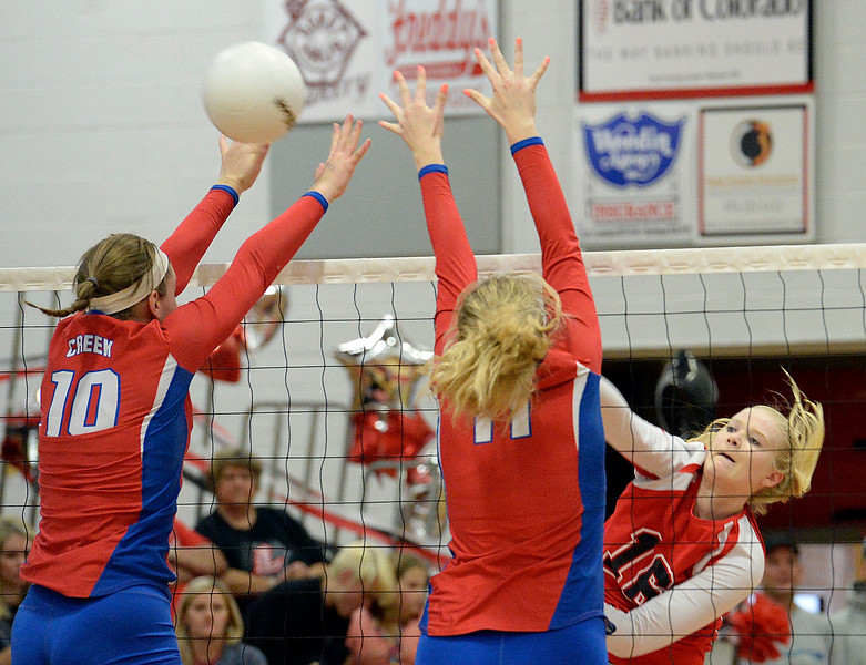 Loveland's #16 Riley Grosboll spikes the ball as Cherry Creek's #10 Katie Sherman and #11 Morgan Owen block during their region 11 volleyball game Saturday, Nov. 5, 2016, at Loveland High School in Loveland. (Photo by Jenny Sparks/Loveland Reporter-Herald)