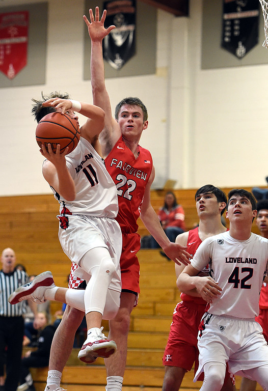 . Loveland\'s Jaxon Cabrera goes up for a shot as Fairview\'s Ashton Nichols tries to block during their game Friday, Jan. 4, 2019, at Loveland High School.   (Photo by Jenny Sparks/Loveland Reporter-Herald)